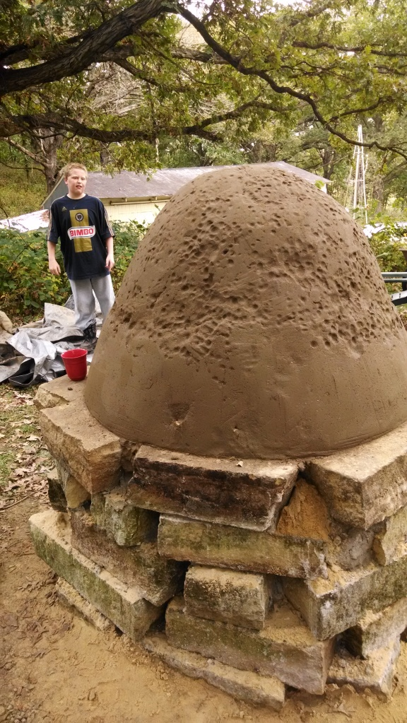 The first layer of cob, applied over a dome of sand.
